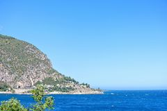 Daylight view to mountains full of bushes and trees. Bright blue sea and clear sky. Negative copy space, place for text. Cap d`Ail, France Stock Image
