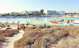 Daylight view to people swiming in the water. AYIA NAPA, CYPRUS - SEPTEMBER 18, 2017: Daylight view to people swiming in the blue water. Hotel in the background Royalty Free Stock Photos