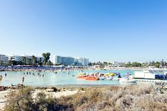 Daylight view to people swiming in the water. AYIA NAPA, CYPRUS - SEPTEMBER 18, 2017: Daylight view to people swiming in the blue water. Hotel in the background Stock Image