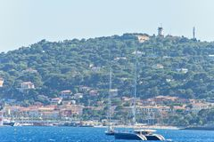 Daylight view to sailing yacht and boats cruising on water. Green trees and buildings on background. Bright blue clear sky. Negative copy space, place for text Royalty Free Stock Photos