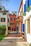 Daylight view to a street of city with vibrant colorful building. S. Shadows and sun shining. Place for text. Burano, Italy royalty free stock photography