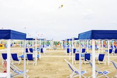 Daylight view to vibrant green sunchairs and sunshades on beach. Daylight view to vibrant blue sunchairs and sunshades on beach. Cloudy sky, kite flying Stock Photography