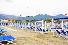 Daylight view to vibrant blue sunchairs and sunshades on beach. Cloudy sky, kite flying buildings and mountains on background. Negative copy space, place for Stock Image