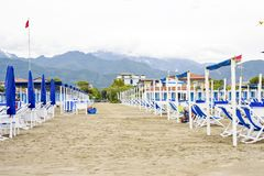 Daylight view to vibrant blue sunchairs and sunshades on beach. Cloudy sky, buildings and mountains on background. Negative copy space, place for text. Forte Royalty Free Stock Photos