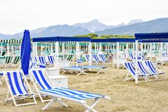 Daylight view to vibrant blue sunchairs and sunshades on beach. Cloudy sky, buildings and mountains on background. Negative copy space, place for text. Forte Stock Images