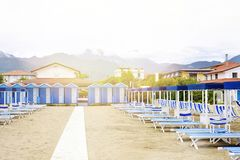 Daylight view to vibrant blue sunchairs and sunshades on beach. Cloudy sky, buildings and mountains on background. Negative copy space, place for text. Forte Royalty Free Stock Image