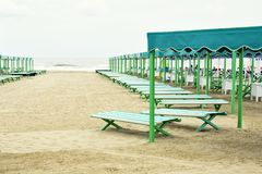 Daylight view to vibrant green and blue sunchairs. And sunshades on beach. Cloudy sky and waves rising on background. Negative copy space, place for text. Forte Stock Photos