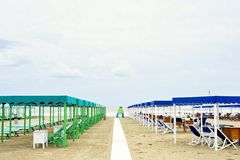 Daylight view to vibrant green and blue sunchairs. And sunshades on beach. Cloudy sky and waves rising on background. Negative copy space, place for text. Forte Royalty Free Stock Image