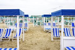 Daylight view to vibrant green sunchairs and sunshades on beach. Daylight view to vibrant blue sunchairs and sunshades on beach. Cloudy sky, buildings and Royalty Free Stock Photo