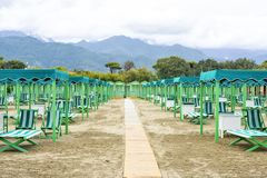 Daylight view to vibrant green sunchairs and sunshades on beach. Cloudy sky, buildings and mountains on background. Negative copy space, place for text. Forte Stock Photos