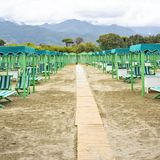Daylight view to vibrant green sunchairs and sunshades on beach. Cloudy sky, buildings and mountains on background. Negative copy space, place for text. Forte Royalty Free Stock Photos