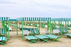 Daylight view to vibrant green sunchairs and sunshades on beach. Cloudy sky and waves rising on background. Negative copy space, place for text. Forte dei Royalty Free Stock Photo