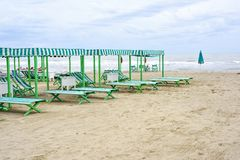 Daylight view to vibrant green sunchairs and sunshades on beach. Cloudy sky and waves rising on background. Negative copy space, place for text. Forte dei Royalty Free Stock Images