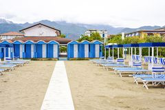 Daylight view to vibrant green sunchairs and sunshades on beach. Daylight view to vibrant blue sunchairs, changing rooms and sunshades on beach. Cloudy sky Royalty Free Stock Images