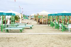Daylight view to vibrant green sunchairs and sunshades on beach. Daylight view to vibrant green and beige sunchairs, sunshades on beach. Cloudy sky on background Royalty Free Stock Images