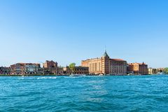 Daylight view from water to Molino Stucky neo-gothic building. And boats cruising on water. Bright blue clear sky. Negative copy space, place for text. Venice Stock Photo