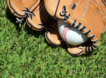 Days Of Baseball. A baseball glove and ball on the outfield grass. It's time for baseball Stock Photo