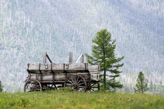Days Gone By. Old weathered wagon with a mountain in the background Stock Photography