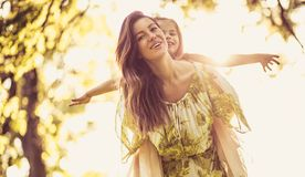 The days are never short of fun when they`re together. Beautiful mother carrying her daughter on piggyback royalty free stock photography