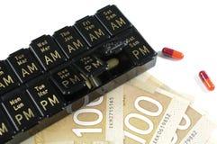 Days of the Week Pillbox. Macro Canadian money and medicine Stock Photos