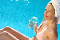 Dayspa. Woman at poolside drinking water Stock Images