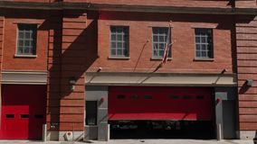Daytime Establishing Shot of City Red Brick Fire Station. A daytime exterior establishing shot of a typical red brick fire station with the garage doors stock video footage