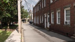 Day Establishing Shot of Empty Alley in Small Town USA. 9186 A daytime establishing shot of an empty alleyway in a small town in America stock video footage