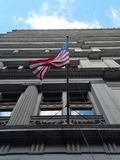 American flag waving on a windy day, view from below, in front of historic office building facade royalty free stock images