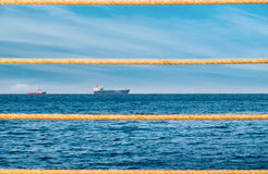 Daytime landscape with ships and ropes. Daytime landscape in the port with ropes in the foreground Royalty Free Stock Image