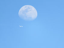 Daytime moon with airplane flying beneath Stock Image