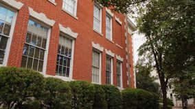 Side morning view of typical red brick school house. A daytime side view exterior establishing shot of a typical red brick school building in a southern American stock video footage