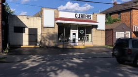 Day exterior establishing shot of cleaners business. A daytime summer exterior establishing shot of a yellow brick building housing a dry cleaners business stock video
