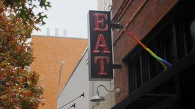 Day view of neon eat sign in city. A daytime view of a red neon EAT sign on the side of a restaurant in a large city. Day/night matching available stock video footage