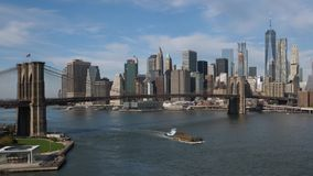 Panoramic Establishing Shot of Lower Manhattan Skyline. A daytime wide establishing shot of the Manhattan Skyline with a barge traveling under the Brooklyn stock footage