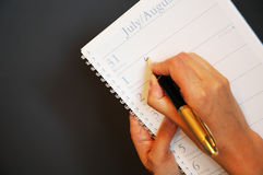 Daytimer Writing. Business person writing in daytimer / diary / work journal stock image
