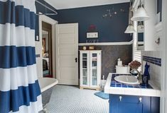 Large Blue & White Bathroom Update. Dayton, Ohio, USA - June 13, 2018: Updated blue & white bathroom of a one hundred-year-old home with tiled sink vanity & Stock Photos