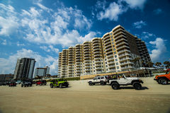 Daytona beach hotels. On the beach at daytona jeep week. lots of jeeps driving up and down the beach against the hotels Stock Photography