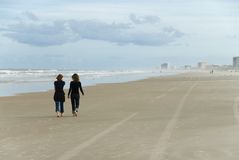 Daytona Beach Walk. Two close friends walk the empty beach and share secrets Royalty Free Stock Photo