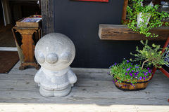 Dazaifu, Japan - May 14, 2017 : Anpanman, popular anime character, granite stone sculpture standing in front of a shop. Along public walkway with flower plant royalty free stock photo