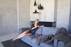 Dazzling blonde uses smartphone and tries ripe strawberry, sitti Stock Photo