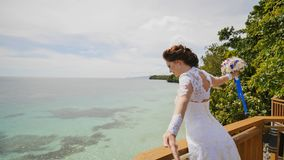 A dazzling bride enjoys happiness from the height of the balcony overlooking the ocean and reefs. Flight of love. Exotic. Filipino Tropics. Shooting in motion stock photo