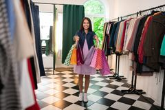 Dazzling female of 30s holding packages in the clothing store. A woman holding packages. Dazzling long-haired charming alluring radiant lovely female of 30s in a stock photos