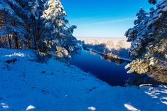 Dazzling sun shining over snowy forest. River flowing along winter woods stock photo