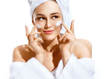 Dazzling young woman applying moisturizing cream on her face Royalty Free Stock Image