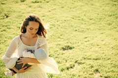 dba dziecka ręk macierzystego obsiadanie Macierzysty cuddle dziecka syn na zielonej trawie zdjęcia royalty free