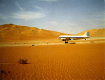 DC-3 taking off in the desert. DC-3 Taking off in the Ar Rab' Al Khali in Saudi Arabia, film scan showing visible grain Stock Photos