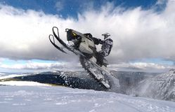 RIDER MAN WITH HELMET JUMPING WITH SNOWMOBILE BETWEEN CLOUDS ON WINTER royalty free stock photos