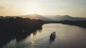 Boat sailing towards Sunset in front of Mountain Ridge. Drone Shot. royalty free stock photography