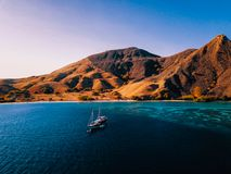 Diveboat in front of half burned Island in Indonesia, Komodo National Park. Drone Shot. royalty free stock photos