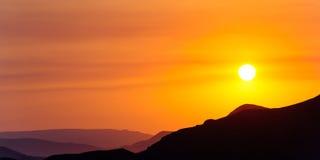 Déclin coloré au-dessus des montagnes Photos libres de droits
